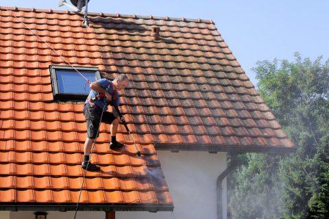 homme nettoyant une toiture