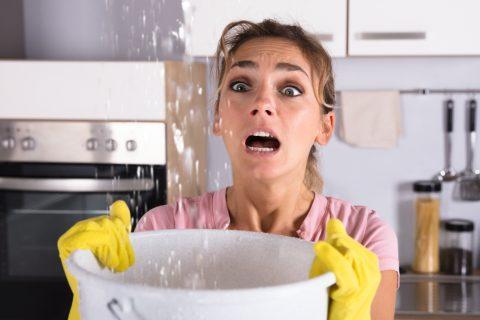 femme tenant un seau pour récupérer l'eau d'une fuite
